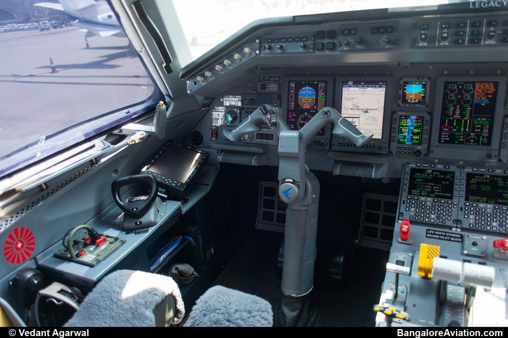 Close up of the captain's seat on the Legacy 600. Behind the yoke, the airport information chart is displayed.