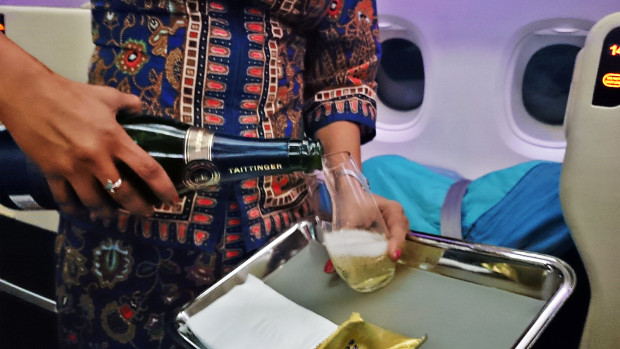 Singapore Airlines stewardess serving Taittinger Prelude Champagne.