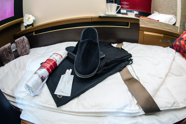 Etihad Boeing 787-9 first class turn-down service, amenity kit (top-left), pyjamas, and herbal tea infusion.